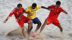 RAVENNA, ITALY - SEPTEMBER 11: Anton Shkarin (L) and Alexey Makarov (R) of Russia and Andre of Brazil battle for the ball during the FIFA Beach Soccer World Cup Final between Russia and Brazil at Stadium del Mare on September 11, 2011 in Ravenna, Italy. (Photo by Dean Mouhtaropoulos - FIFA/FIFA via Getty Images)