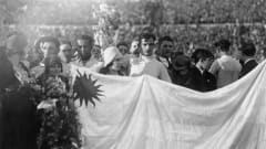 Uruguayan goalkeeper Enrique Ballesteros (centre) holding a bouquet of flowers as the team, fans, and officials line up behind the national flag during the celebrations at the end of the 1930 FIFA World Cup Final between Uruguay and Argentina at the Estadio Centenario in Montevideo, 30th July 1930. Uruguay won 4-2. (Photo by Bob Thomas/Popperfoto/Getty Images)