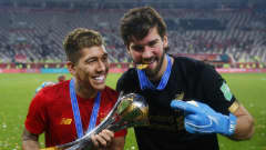 DOHA, QATAR - DECEMBER 21: Roberto Firmino and Alisson Becker of Liverpool pose with the FIFA Club World Cup trophy following their victory in the FIFA Club World Cup Qatar 2019 Final between Liverpool FC and CR Flamengo at Education City Stadium on December 21, 2019 in Doha, Qatar. (Photo by Francois Nel/Getty Images)