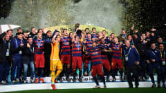 YOKOHAMA, JAPAN - DECEMBER 20:  Barcelona players and coaching staff celebrate as captain Andres Iniesta of Barcelona lifts the trophy, following their 3-0 victory during the FIFA Club World Cup Final between River Plate and FC Barcelona at the International Stadium Yokohama on December 20, 2015 in Yokohama, Japan.  (Photo by Shaun Botterill - FIFA/FIFA via Getty Images)