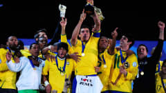 JOHANNESBURG, SOUTH AFRICA - JUNE 28: Lucio of Brazil lifts the trophy as his team mates celebrate following their victory at the end of the FIFA Confederations Cup Final between USA and Brazil at the Ellis Park Stadium on June 28, 2009 in Johannesburg, South Africa. (Photo by Jamie McDonald/Getty Images)
