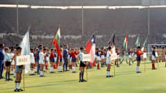 11 July, Wembley, the 1966 FIFA World Cup begins. Schoolboys from London stand on the pitch wearing the colours and bearing the flags of the sixteen participating nations in the opening ceremony of the tournament. Chile, whose flag can be seen in the centre, hosted the 1962 World Cup.