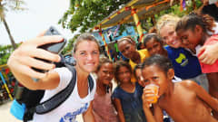 Louise Fleury of France takes a selfie with locals during a visit to Fisherman's Island