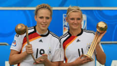 BIELEFELD, GERMANY - AUGUST 01:  Kim Kulig (L) of Germany and Alexandra Popp pose with the bronze and golden trophy after the 2010 FIFA Women's World Cup Final match between Germany and Nigeria at the FIFA U-20 Women's World Cup stadium August 01, 2010 in Bielefeld, Germany.  (Photo by Martin Rose - FIFA/FIFA via Getty Images)