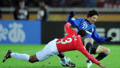 Gamba Osaka's Hideo Hashimoto fights for the ball with Manchester United's Patrice Evra