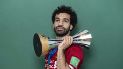 DOHA, QATAR - DECEMBER 21: Mohamed Salah of Liverpool poses with the Club World Cup trophy after the FIFA Club World Cup Qatar 2019 Final match between Liverpool and CR Flamengo at Khalifa International Stadium on December 21, 2019 in Doha, Qatar. (Photo by David Ramos - FIFA/FIFA via Getty Images)