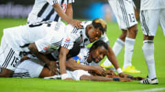 ABU DHABI, UNITED ARAB EMIRATES - DECEMBER 14: Mulota Kabangu of TP Mazembe Englebert is mobbed by team mates as he celebrates scoring to make it 1-0 during the FIFA Club World Cup 2010 match between TP Mazembe Englebert and SC Internacional at Mohamed Bin Zayed Stadium on December 14, 2010 in Abu Dhabi, United Arab Emirates. (Photo by Michael Regan - FIFA/FIFA via Getty Images)