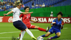 MONTREAL, QC - AUGUST 24: Clarisse Le Bihan of France tries to score against Ri Un Yong and goalkeeper Kim Chol Ok of Korea DPR (L-R) during the FIFA U-20 Women's World Cup Canada 2014 3rd place match between Korea DPR and France at Olympic Stadium on August 24, 2014 in Montreal, Canada.  (Photo by Alex Grimm - FIFA/FIFA via Getty Images)